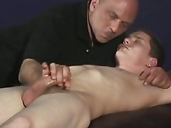 A man is jerking a sleeping guys cock