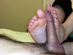 Lucky guy has a pair of sensual feet caressing his meat pole