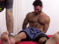 Hairy Chase is restrained down in bed for a tickle session